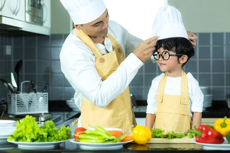 Healthy Family. Father and kid boy cooking and cutting vegetables for diet in kitchen.  Smiling son  help  making cookie, so happy and enjoy in holiday.  Healthy and Family Concept. 写真素材