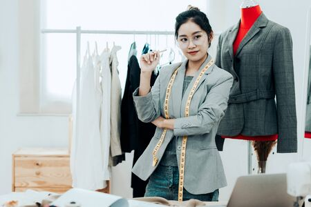 Asian young women fashion designer  working on her designer in the showroom,  Lifestyle Stylish tailor taking measurements on mannequin in studio.  Business small Concept