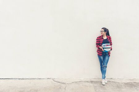 Asian lifestyle woman standing and holding book for education outdoors,  free space over white brick wall.  Education Concept 写真素材
