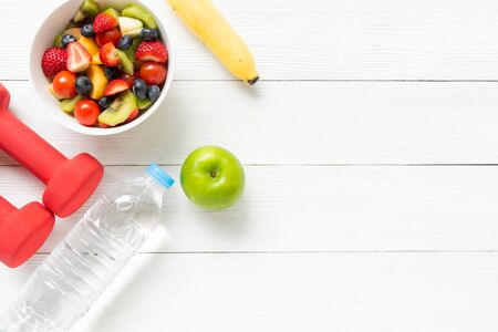 Healthy Fruits.  Fresh fruits salad diet slim fit with dumbbells sport equipment, water and banana for healthy lifestyle women.  Weight Loss and Diet Concept