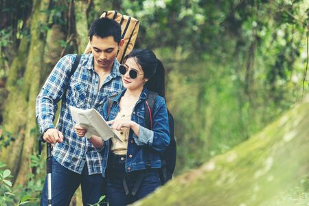 Couple asian traveler with backpack adventure holding map to find directions and walking relax in the jungle forest outdoor for destination leisure education nature on vacation. Travel and Lifestyle C