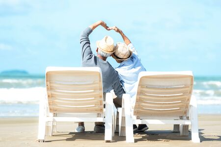 Asian Lifestyle senior couple raise hands and sitting on the beach happy in love romantic and relax time. Tourism elderly family travel leisure and activity after retirement vacations and summer. 写真素材