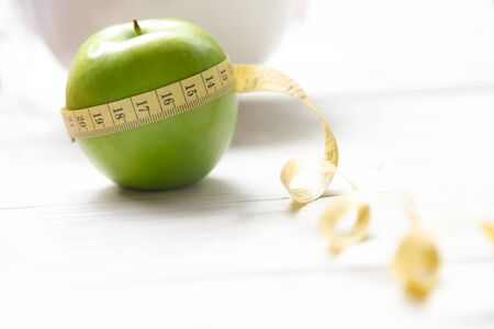 Diet and Healthy life loss weight Concept. Green apple and Weight scale measure tap with fresh vegetable and sport equipment for women diet slimming