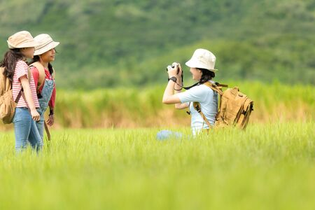 Asian group family and friend children take a photo in the meadow.  Tourism for destination leisure trips for education adventure and relax outdoors forest nature. Travel vacations Concept 写真素材