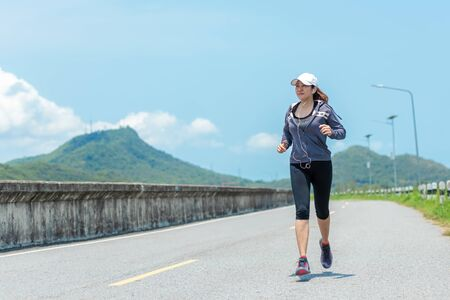 Sporty Woman runner running through the road.  Outdoor Workout jogging in a road dam. Weight Loss and Healthy Concept 写真素材