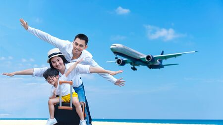 Asian happy family have fun on the beach watching the landing planes. Traveling on an airplane for leisure and destination.  Family tourism travel in summer and holiday.  Copy space for banner in text