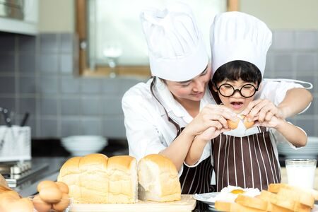 Healthy Family.   Asian little boy help mother cooking toast and make bread in holiday.  People family making and leaning sweet food, so happy and enjoy.  Family and Lifestyle Concept.