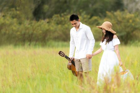 Lifestyle couple picnic sunny time. Asian young couple having fun and walking relax in the meadow and field in holiday.  Romantic and In love.   Lifestyle concept