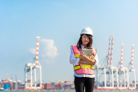 Asian women engineer holding laptop and working with container Cargo freight ship in shipyard at dusk for Logistic Import Export background, safety control. Engineer Concept