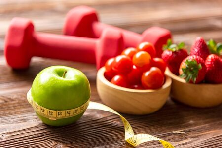 Healthy lifestyle for women diet with fresh fruits salad and dumbbells sport equipment measuring tape, fruit healthy green apples on wooden.  Healthy Concept. select focus 写真素材