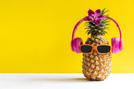 Summer in the party.  Hipster Pineapple Fashion in sunglass and music bright beautiful color in holiday, Creative art fruit for tropical style on the beach vibes, yellow background.  Fashion Summer Va