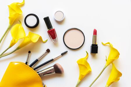 Makeup cosmetics tools and beauty cosmetics gift, products and facial cosmetics package lipstick with yellow lily flower on the white background, top view and copy space.  Lifestyle Beauty Concept
