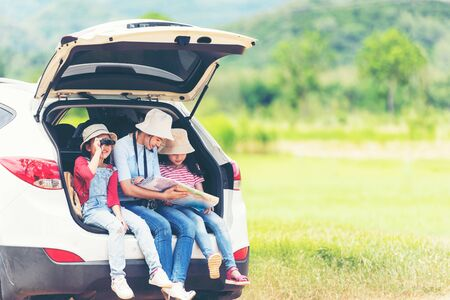 Group asian family children checking map and pointing on the car adventure and tourism for destination leisure trips travel for education and relax in nature park.  Travel vacations