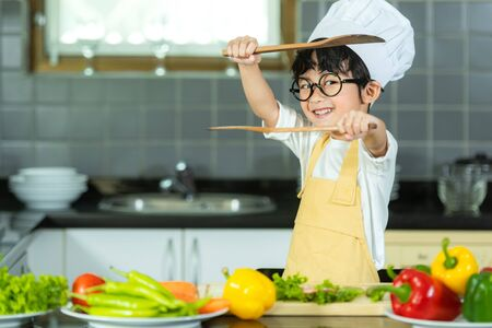Asian little boy cooking and cutting vegetables for mixed healthy salad in the  kitchen, so happy and relax for leaning and education cook food.  Lifestyle and Family Concep.  select focus 写真素材