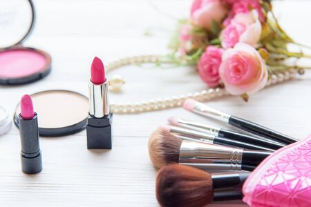Gift Cosmetic.  Makeup cosmetics tools background and beauty cosmetics, products and facial cosmetics package lipstick, eyeshadow with pink rose and pearl necklace on the white background, vintage ton