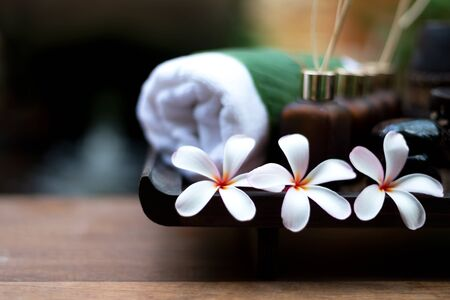 Thai spa composition treatments aroma therapy with candles and Plumeria flowers on wooden table close up. Healthy and Relax Concept 写真素材