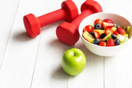 Healthy lifestyle for women diet with fresh fruits salad and dumbbells sport equipment, fruit healthy green apples on wooden.  Healthy Concept. Banque d'images - 131766840