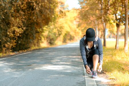 Running asian woman tying laces of running shoes before jogging through the road in the workout nature autumn park. Weight Loss and Healthy Concept