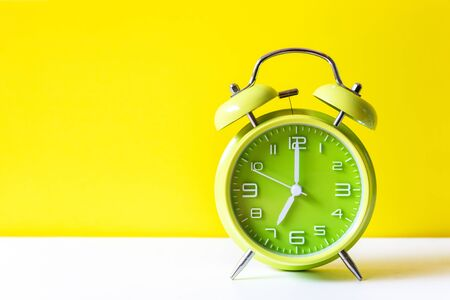 Alarm green vintage alarm clock falling on the floor with color background. Morning and Start up Concept 写真素材