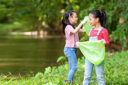 Group family asian children collecting garbage and plastic on the river to dumped into the trash for volunteer charity save environment. Ecology earth Concept. Stock Photo