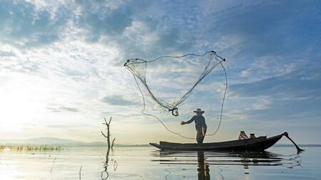 Reflection fisherman action when fishing net with dry alone tree on the boat in the lake outdoors, sunshine morning. Agriculture Industry