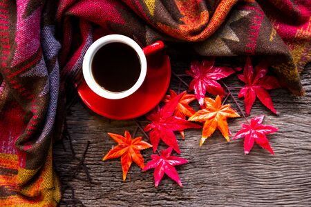 Seasonal autumn leaves.  Cup coffee hot steaming  warm scarf on wooden table background in morning relax sunny day. Lifestyle concept Banco de Imagens