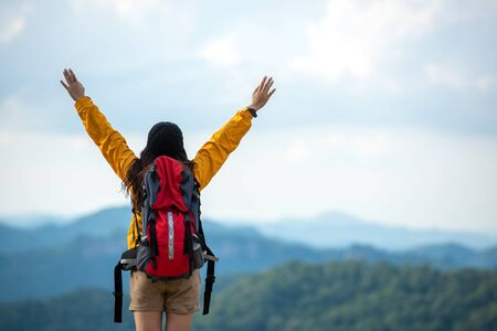 Hiker asian women raise hand and pointing happy feeling freedom good and strong weight victorious facing on the natural mountain. Traveler going camping outdoors destination leisure