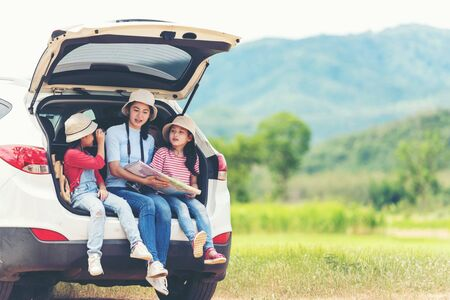 Group asian family children checking map and pointing on the car adventure and tourism for destination and leisure trips travel for education and relax in nature park .  Travel vacations 版權商用圖片