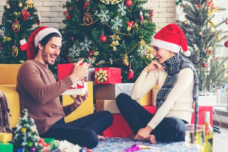 Merry Christmas. girlfriend surprising his boyfriend with Christmas gift. Young couple celebrating and party and drinking champagne new year and Christmas with present and Christmas tree at home.