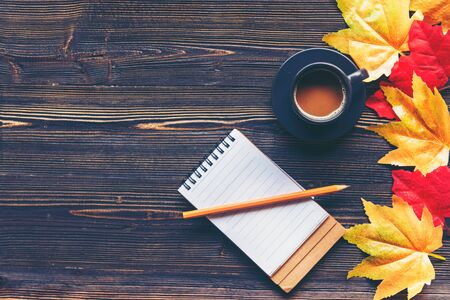 Seasonal autumn maple leaves.  Cup coffee hot steaming  warm scarf with paper note for greeting text on wooden table background in morning relax sunny day. Lifestyle concept