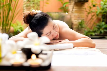 Asian woman lying down on massage bed with scrub sugar and salt aroma at outdoor natural.  wellness center, so relax and lifestyle. Thai Day Spa.  Healthy Concept