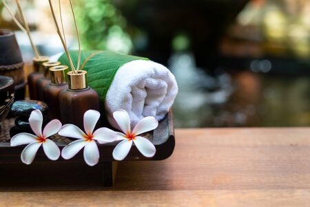 Thai spa composition treatments aroma therapy with candles and Plumeria flowers on wooden table close up. Healthy and Relax Concept Stock Photo