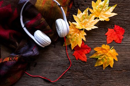 Cozy winter background marshmallow, headphones and leaves maple relax on season autumn, warm knitted sweater on old wooden background.  Lifestyle concept