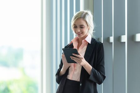 Business women using smart phone or mobile to work and checking information of financial data and connection technology in model office city town.   Business Concept.
