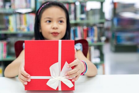 Gift box for kids girl. White box with red bow in the smiling asian girl hands for give a gift in the library, happy and surprise gift in the box. Anniversary and Celebration Concept
