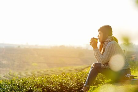 Asian lifestyle women wearing sweater, sitting and drinking hot coffee or tea relax outdoor in the sunrise morning sunny day at tea plantation nature.  Lifestyle Concept.