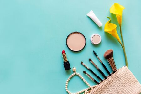 Makeup cosmetics tools and beauty cosmetics gift, products and facial cosmetics package lipstick with yellow lily flower on the blue background, top view and copy space.  Lifestyle Beauty Concept