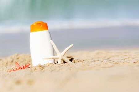 Protective sunscreen or sunblock and sunbath lotion for healthy care skin woman in white plastic bottles with starfish on tropical beach, summer accessories in holiday, copy space for text.  Summer Concept