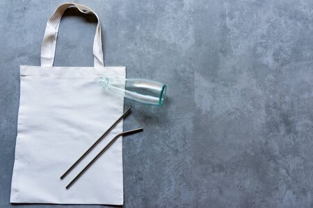 Saving Earth. White tote bag canvas package and fabric cloth eco shopping with Stainless tube, glass bottle on blackboard background. Save environment Concept