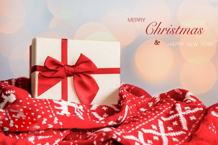 Merry Christmas. Red gift box with red sweater celebrating and party Christmas at home. Yellow bokeh background.