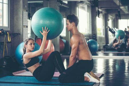 Trainer training yoga ball and exercise with  woman at the gym for healthy care and body slim.  Fitness instructor exercising with his client people the fitness. Healthy sport Concept Stock Photo