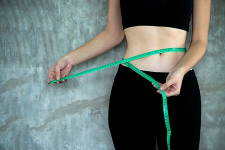 Lifestyle woman hands measuring waist with a tape for body slim. Healthy woman exercise on the fitness class. Diet and Healthy life loss weight Concept. Stock Photo