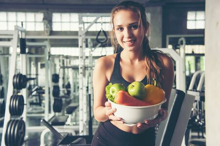 Lifestyle women hold fresh salad after exercise  at the gym workout for healthy care and body slim.  Fitness instructor exercising the fitness. Diet and Healthy sport Concept