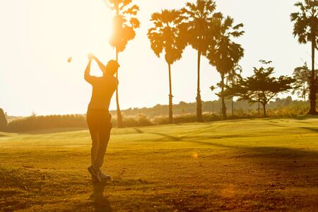 Silhouette Professional Golfer asian man swing and hitting golf ball practice at golf driving range and fairway in sunny morning day on multiethnic club golf. Lifestyle and Sport Concept