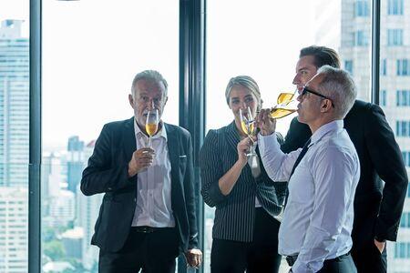 Entspannen Sie sich. Business-Teamwork und Partner feiern Champagner nach dem Treffen und präsentieren ein neues Projekt in einem modernen Büro. Stadt Hintergrund. Geschäfts- und Teamwork-Konzept Standard-Bild