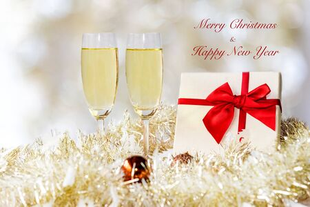Merry Christmas. Champagne in two glasses and red gift box celebrating and party Christmas at home. Yellow bokhe background.