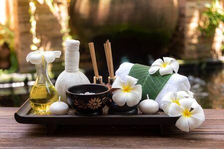 Thai Spa Komposition Behandlungen Aromatherapie mit Kerzen und Plumeria Blumen auf Holztisch hautnah. Gesundes und entspannendes Konzept