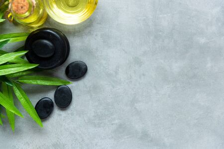 Thai Spa. Hot stones setting for massage treatment and relax on blackboard with copy space. Green leaf with black stones pile for spa therapy. Lifestyle Healthy