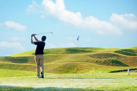 Professional golfer asian man approach on the tee off for swing and hitting golf ball and looking fairway in course. Hobby in holiday and vacations in sunny morning day on club golf. Lifestyle, and sport Concept. Stock fotó