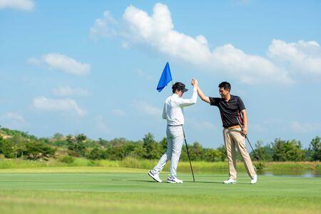 Group Professional Golfer asiatischer Mann schütteln die Hand für Freundschaft, nachdem der Ball auf das Grün gelegt wurde. Hobby entspannen im Urlaub und Urlaub mit Freunden. Lifestyle- und Sportkonzept